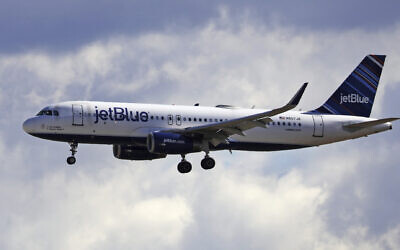 In this Oct. 18, 2019, file photo a JetBlue Airways flight flies in to Salt Lake City International Airport (AP Photo/Rick Bowmer)