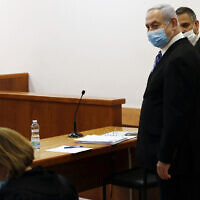 Prime Minister Benjamin Netanyahu, wearing a face mask in line with public health restrictions due to the coronavirus pandemic, stands inside the courtroom as his corruption trial opens at the Jerusalem District Court, May 24, 2020 (Ronen Zvulun/ Pool Photo via AP)