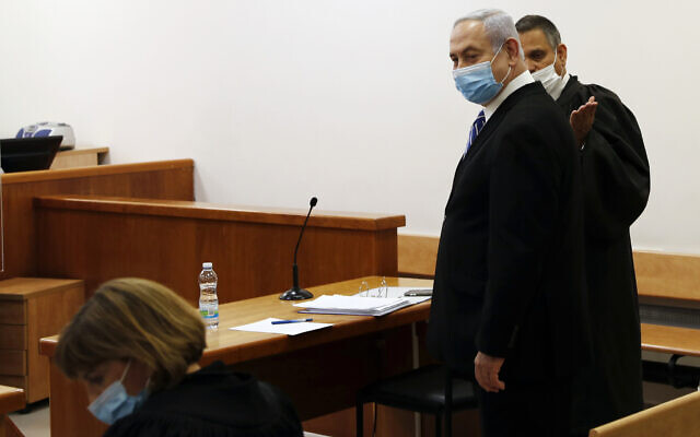 Prime Minister Benjamin Netanyahu, wearing a face mask in line with public health restrictions due to the coronavirus pandemic, stands inside the courtroom as his corruption trial opens at the Jerusalem District Court, May 24, 2020. (Ronen Zvulun/ Pool Photo via AP)