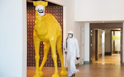 An Emirati wearing a face mask, due to the coronavirus pandemic, walks past a camel statue decorated with a face mask, at the Rove City Centre Hotel in Dubai, United Arab Emirates, July 6, 2020. (AP/Jon Gambrell)