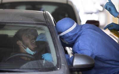 A man is tested by a healthcare worker for the coronavirus at a drive-thru testing center in Tel Aviv on July 6, 2020. (AP Photo/Sebastian Scheiner)