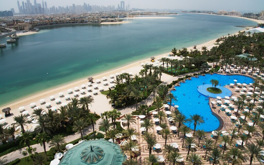 The pool and beach of the Atlantis Hotel is seen with the skyline of the Dubai Marina visible in the distance in Dubai, United Arab Emirates, Tuesday, July 14, 2020. (AP Photo/Jon Gambrell)
