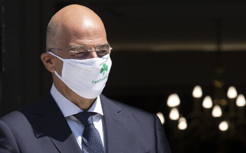 Illustrative: Greek Foreign Minister Nikos Dendias, wearing a face mask of Panathinaikos looks on during the arrival of his Spanish counterpart Arancha Gonzalez Laya before their meeting in Athens, July 28, 2020. (AP Photo/Petros Giannakouris)