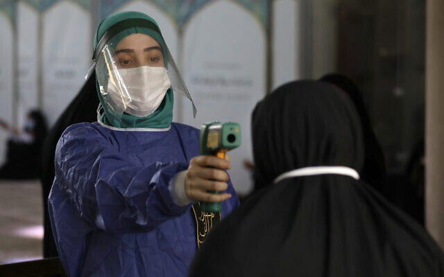 A volunteer wearing protective gear to help prevent the spread of the coronavirus checks temperature of a worshiper as she enters the mosque of Tehran University to pray during Arafat Day, Iran, July 30, 2020. (Vahid Salemi/AP)
