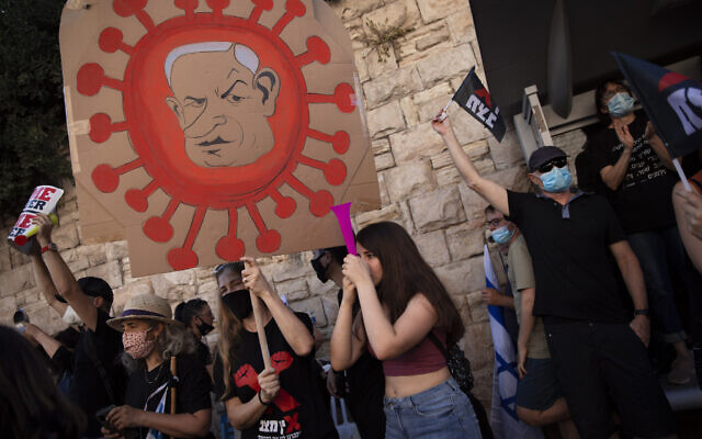 A protester holds a sign depicting Prime Minister Benjamin Netanyahu during a protest a against him outside his residence in Jerusalem, July 31, 2020. (AP/Oded Balilty)