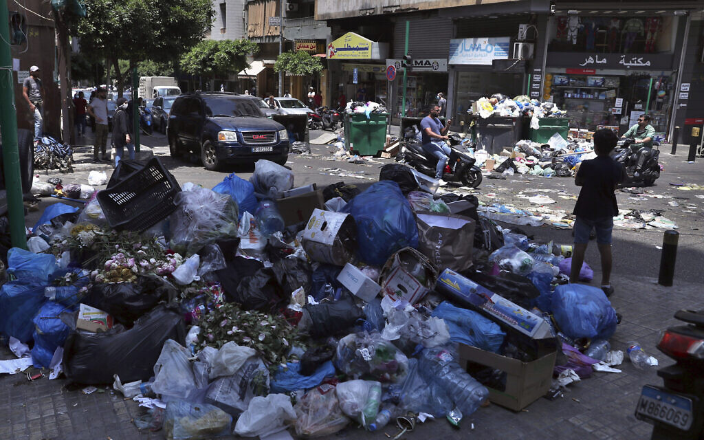 In this July 14, 2020, photo, a road is partially blocked with garbage and bins in protest of uncollected trash, in Beirut, Lebanon (AP Photo/Bilal Hussein)