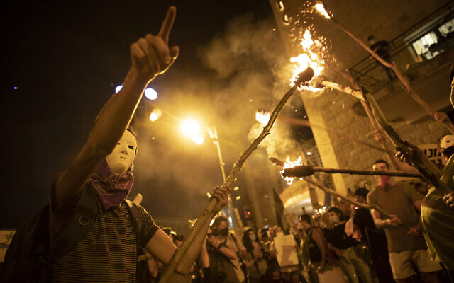 Protesters light torches during a protest against Prime Minister Benjamin Netanyahu outside his official residence in Jerusalem, August 1, 2020. (AP Photo/Oded Balilty)