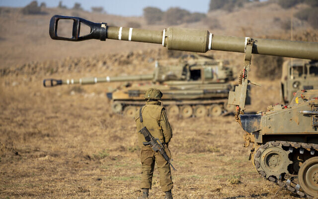 An Israeli soldier stands next to a mobile artillery unit during an exercise in the Golan Heights on August 4, 2020. (Ariel Schalit/AP)