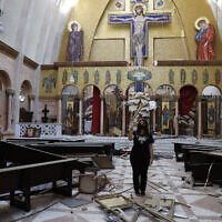 A woman takes pictures of a damaged church, after an explosion hit the seaport of Beirut, Lebanon, August 5, 2020. (AP Photo/Hussein Malla)