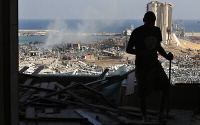 A man stands in a damaged apartment as he looks out at the scene of a massive explosion that hit the seaport of Beirut, Lebanon, August 5, 2020. (Hussein Malla/AP)