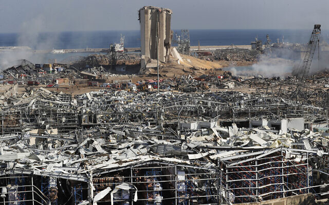 Rescue workers and security officers work at the scene of an explosion that hit the seaport of Beirut, Lebanon, August 5, 2020. (AP Photo/Hussein Malla)