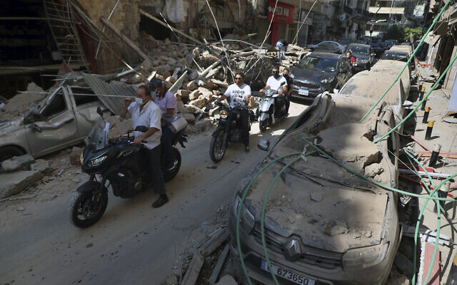 People drive past buildings and cars that were damaged in the previous day's massive explosion in the seaport of Beirut, Lebanon, August 5, 2020. (AP Photo/Bilal Hussein)