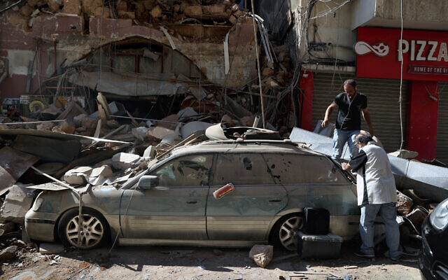 People inspect their car, damaged in the previous day's massive explosion in the seaport of Beirut, Lebanon, August 5, 2020. (AP/Bilal Hussein)