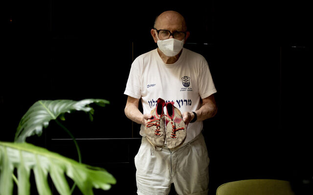Israeli Olympic racewalker Shaul Ladany holds his 1972's Olympic race shoes for a portrait in Omer, Israel, July 12, 2020. (Ariel Schalit/AP)