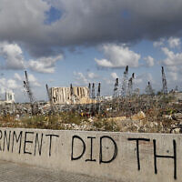Words are written by Lebanese citizens in front of the scene of Tuesday's explosion that hit the seaport of Beirut, Lebanon, Sunday, Aug. 9, 2020. Public fury over the massive explosion in Beirut took a new turn Saturday night as protesters stormed government institutions and clashed for hours with security forces, who responded with heavy volleys of tear gas and rubber bullets. (AP Photo/Hussein Malla)
