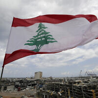 A Lebanese flag set by citizens flies in front the site of Tuesday's explosion that hit the seaport of Beirut, Lebanon, Sunday, Aug. 9, 2020. Lebanon's information minister resigned on Sunday as the country grapples with the aftermath of the devastating blast that ripped through the capital and raised public anger to new levels. (AP Photo/Hassan Ammar)