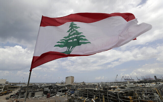 A Lebanese flag set by citizens flies in front the site of an explosion that hit the seaport of Beirut, Lebanon, August 9, 2020. (AP Photo/Hassan Ammar)