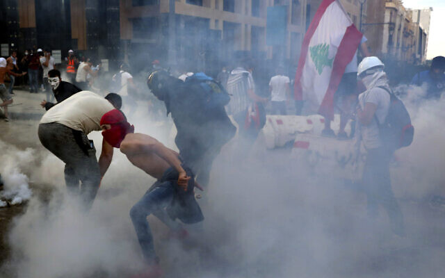 Anti-government protesters throw back tear gas canisters towards riot policemen on Monday, August 10, 2020. (AP/Bilal Hussein)