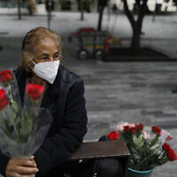 "Wearing a mask to curb the spread of the new coronavirus, Martha Gonzalez Reyes, 76, sells roses outside Metro Hidalgo in central Mexico City, Monday, Aug. 10, 2020. After four months staying at home, Gonzalez returned to selling on August 1, but she says business hasn't fully rebounded. ""People have less money to spend she says, and they don't want to go out and get infected.""(AP Photo/Rebecca Blackwell)"
