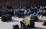 Passengers sit next to their luggage as they wait to cross the border to the Egyptian side of Rafah crossing, in Rafah, Gaza Strip, August 11, 2020. (AP Photo/Adel Hana)