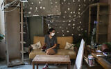 Rachelle Boumelhem sits in her damaged beauty salon in Beirut, Lebanon, Aug. 10, 2020 (AP Photo/Felipe Dana)