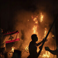 Anti-government protesters burn a barricade next to a wall installed by security forces to block access to the Parliament building, during a demonstration following last week's massive explosion which devastated Beirut, Lebanon, Aug. 11, 2020. (AP Photo/Felipe Dana)