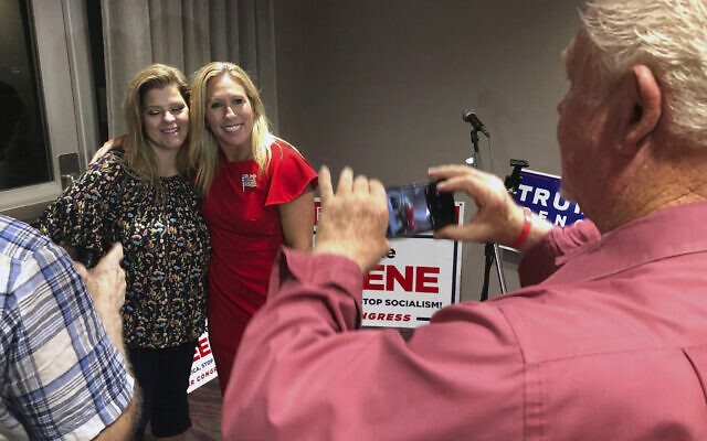 Supporters take photos with Republican conspiracy theorist Marjorie Taylor Greene, background right, in Rome, Georgia, August 11, 2020. (AP Photo/Mike Stewart)