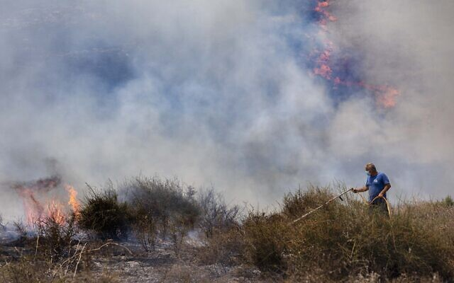 An Israeli worker from the Nature and Parks Authority attempts to extinguish a fire caused by a incendiary balloon launched by Palestinians from the Gaza Strip, on the Israeli side of the border between Israel and Gaza, near Or HaNer Kibbutz, Wednesday, Aug. 12, 2020. (AP/Tsafrir Abayov)