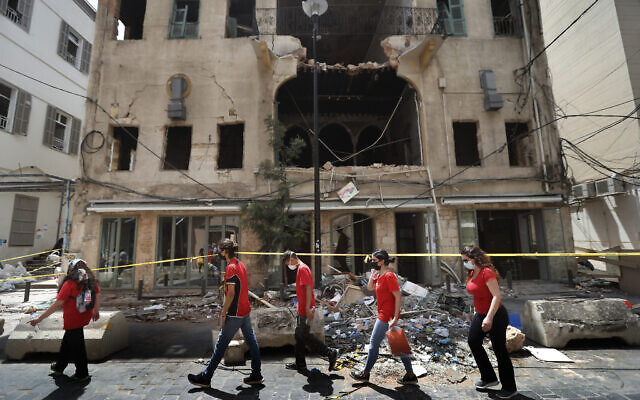 University students who volunteered to help clean damaged homes and give other assistance, pass in front of a building that was damaged by last week's explosion, in Beirut, Lebanon, Aug. 11, 2020 (AP Photo/Hussein Malla)
