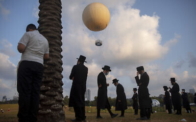 Ultra-Orthodox Jews, some wearing protective face mask amid concerns over the country's coronavirus outbreak, pray at a park in Tel Aviv, Israel, Aug. 12, 2020 (AP Photo/Oded Balilty)
