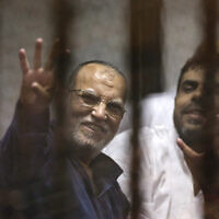 Senior Muslim brotherhood leader Essam el-Erian, left, flashes the four-fingered symbol of Rabaah that refers to the deadly dispersal of supporters of former Egyptian President Mohammed Morsi in August 2013, inside a makeshift courtroom at Egypt's National Police Academy, in Cairo, Egypt, on April 21, 2015. (AP Photo/Amr Nabil, File)