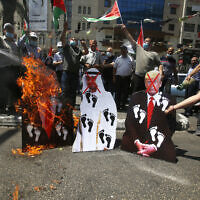 Palestinians burn pictures of U.S. President Donald Trump, Abu Dhabi Crown Prince Mohammed bin Zayed al-Nahyan and and Prime Minister Benjamin Netanyahu during a protest against the United Arab Emirates' deal with Israel, in the West Bank city of Nablus, Friday, August 14, 2020. (AP Photo/Majdi Mohammed)