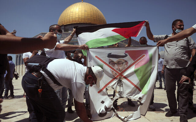 Palestinian protesters burn a banner showing Abu Dhabi Crown Prince Mohamed bin Zayed al-Nahyan near the Dome of the Rock on the Temple Mount in Jerusalem's Old City, August 14, 2020. (AP Photo/Mahmoud Illean)
