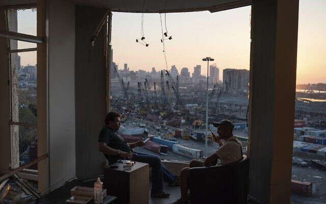 Two men sit on the destroyed balcony of a building facing the site the massive explosion in the port of Beirut, Lebanon, August 14, 2020. (AP Photo/Felipe Dana)