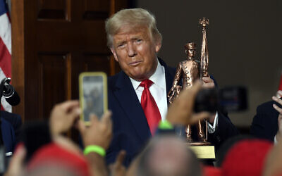 US President Donald Trump holds a statue presented to him as he speaks during an event Trump National Golf Club, Aug. 14, 2020, in Bedminster, N.J., with members of the City of New York Police Department Benevolent Association. (AP Photo/Susan Walsh)