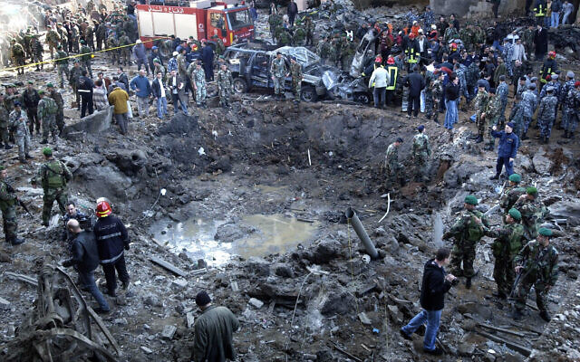 Rescue workers and soldiers stand around a massive crater after a bomb attack that tore through the motorcade of former Prime Minister Rafik Hariri, in Beirut, Lebanon, February 14, 2005. (AP Photo)