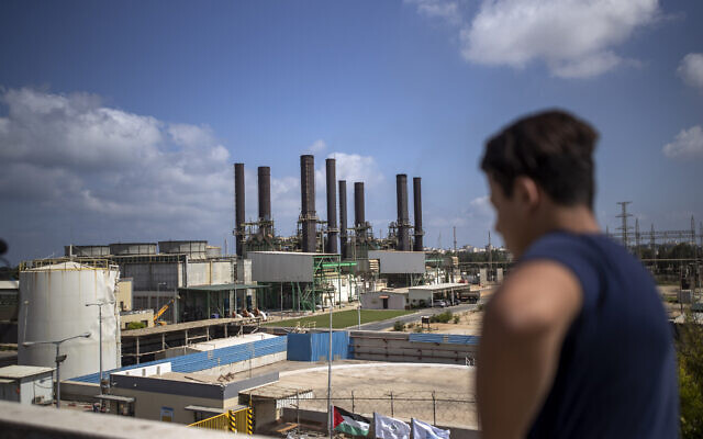 A Palestinian man, on the rooftop of his home, looks at Gaza's power plant after it was shut down, in the town of Nusairat, central Gaza Strip, August 18, 2020. (AP Photo/ Khalil Hamra)
