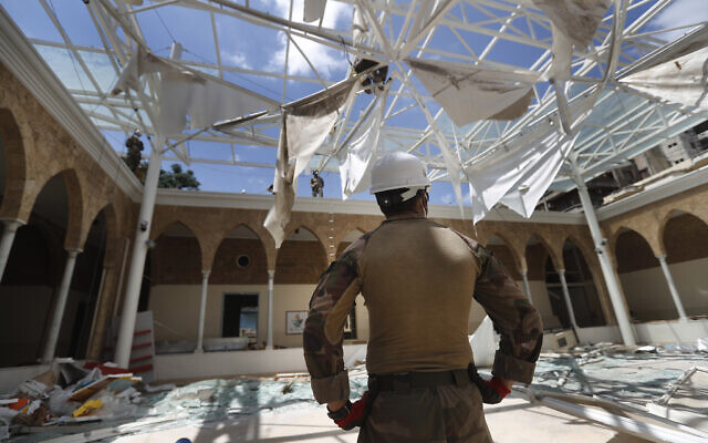 A French soldier looks at his comrades removing the debris of a school playground roof that was destroyed by Aug. 4 explosion that hit the seaport of Beirut, Lebanon, Aug. 20, 2020 (AP Photo/Hussein Malla)