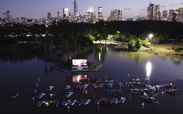 People watch a movie from small boats at 'sail-in' floating cinema at HaYarkon Park's boating lake in Tel Aviv, Israel, Aug. 20, 2020 (AP Photo/Oded Balilty)