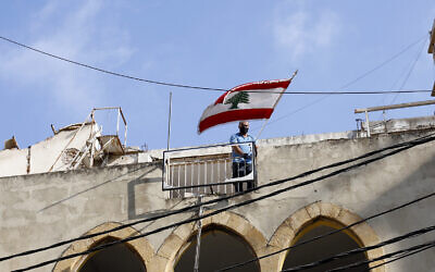 In this Friday, Aug. 7, 2020, file photo, a man puts a Lebanese flag on the roof of a damaged building at a neighborhood near the scene of an explosion that hit the seaport of Beirut, Lebanon (AP Photo/Thibault Camus, File)
