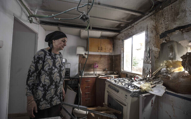Homeowner Osnat Malka inspects damage from a rocket fired overnight from the Gaza Strip, in Sderot, Israel, Aug. 21, 2020 (AP Photo/Tsafrir Abayov)
