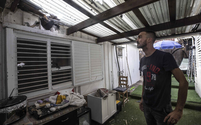 An Israeli man inspects the damage to a home after it was hit by a rocket fired from the Gaza Strip, in Sderot, Israel, Aug. 21, 2020 (AP Photo/Tsafrir Abayov)