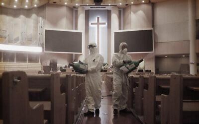 Public officials disinfect pews as a precaution against the coronavirus at the Yoido Full Gospel Church in Seoul, South Korea, Aug. 21, 2020 (AP Photo/Ahn Young-joon)