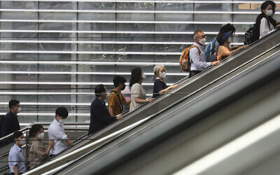 People wearing face masks to help protect against the spread of the coronavirus ride an escalator as they arrive at the Seoul Railway Station in Seoul, South Korea, August 24, 2020. (AP Photo/Ahn Young-joon)