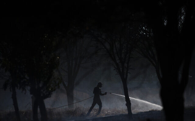 A volunteer attempts to extinguish a fire started by an incendiary device launched from the Gaza Strip, on the Israeli side of the border between Israel and Gaza, Monday, Aug. 24, 2020.  (AP Photo/Ariel Schalit)
