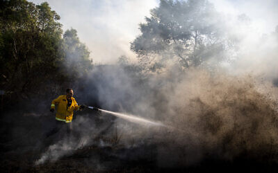 A firefighter attempts to extinguish a fire started by an incendiary device launched from the Gaza Strip, in Kibbutz Kfar Aza on the border with Gaza, August 24, 2020. (AP/Ariel Schalit)