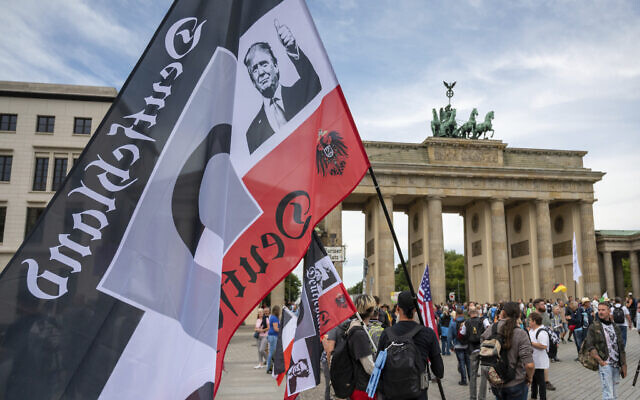 A protestor holds a flag of the German Reich with a picture of US President Donald Trump in front of the Brandenburg Gate before a demonstration against the coronavirus measures by the German Government in Berlin, Germany, Aug. 29, 2020. (Christophe Gateau/dpa via AP)