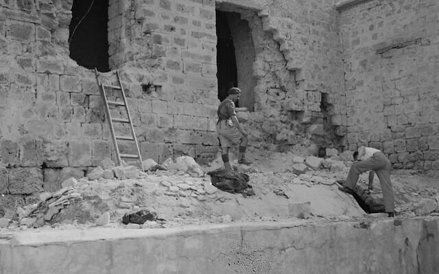 Two men look over debris beneath shattered windows of Acre Prison, north of Haifa, British-Mandate Palestine, May 6, 1947, which was blasted open two days earlier by members of an underground Jewish militia. (AP Photo)