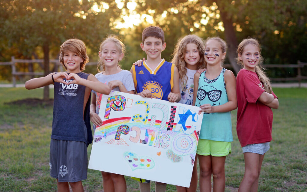 Campers at Camp Young Judaea Texas hold a Hebrew sign that translates as 'We love you.' (Courtesy of authors)