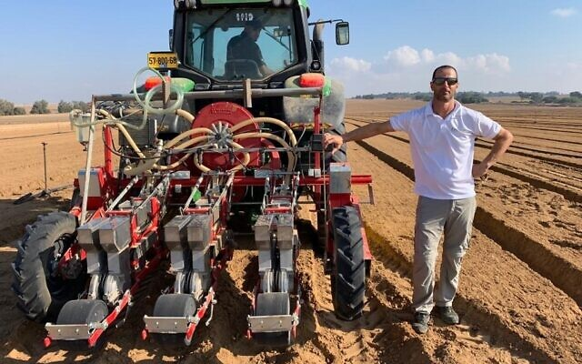 Dotan Borenstein, CEO of SaliCrop, stands next to a tractor distributing carrot seeds for a field trial near the Gaza border, August 23, 2020. (Courtesy)